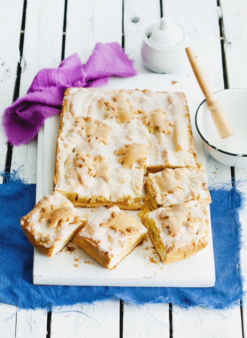 Ein Gedeckter Apfelkuchen ist in Stücke geschnitten und liegt auf einem Holzbrett serviert.