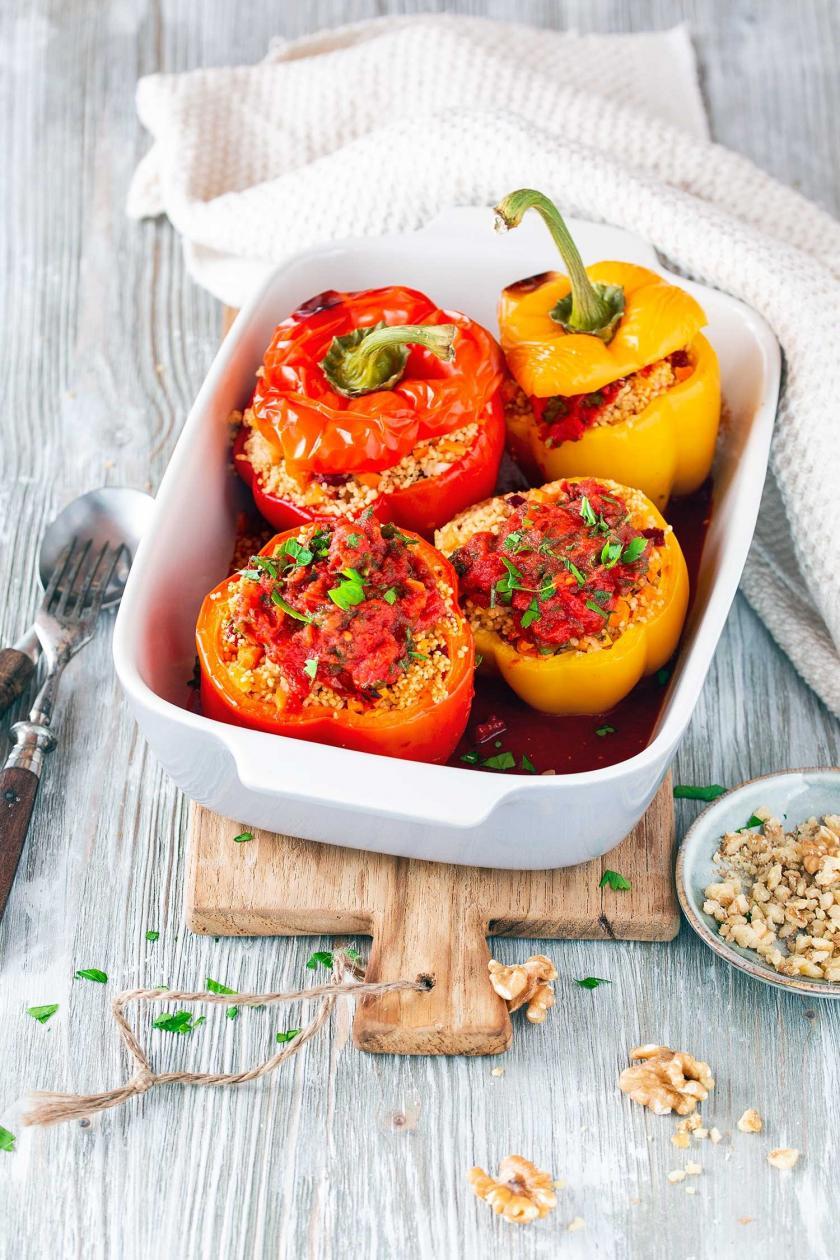 Mehrere gefüllte Paprika mit Couscous in einer Auflaufschale.