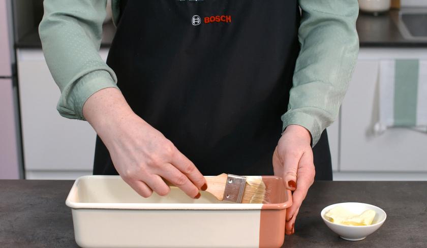 Für den gefüllter Schoko-Erdbeerkuchen wird eine Kastenform eingefettet.