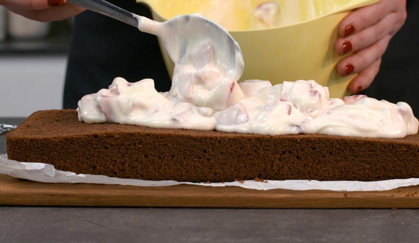 Die Füllung für gefüllter Schoko-Erdbeerkuchen wird auf einer Kuchenhälfte verteilt.