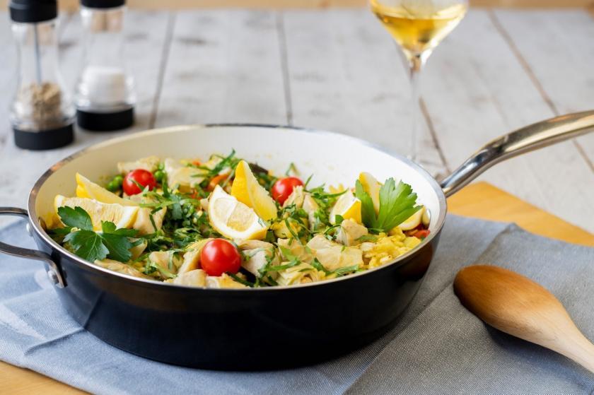 Pfanne mit Gemüse-Paella auf weißem Holztisch