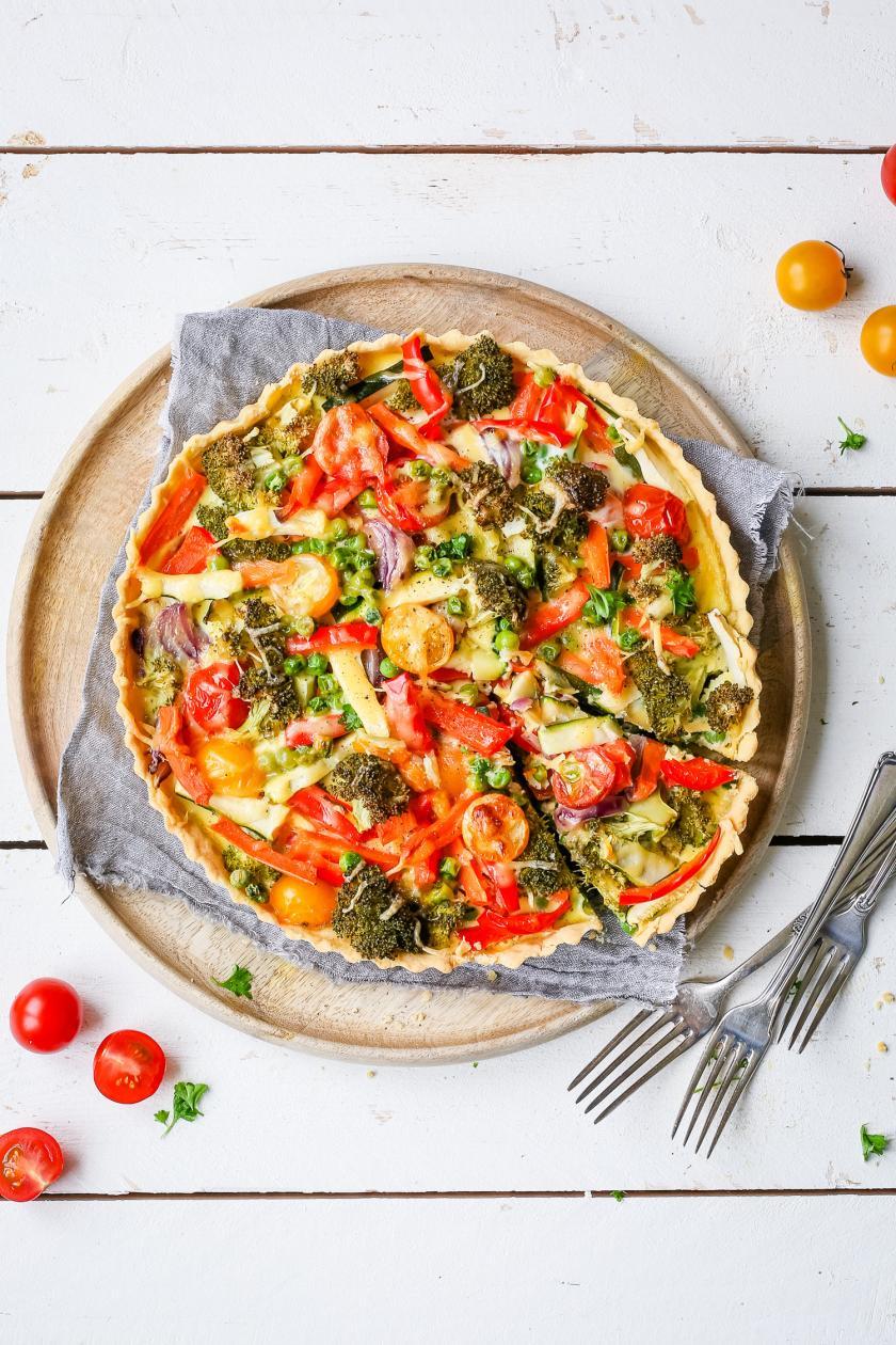 Gemüsequiche angeschnitten mit Tomaten, Paprika, Erbsen, Zucchini und Möhren
