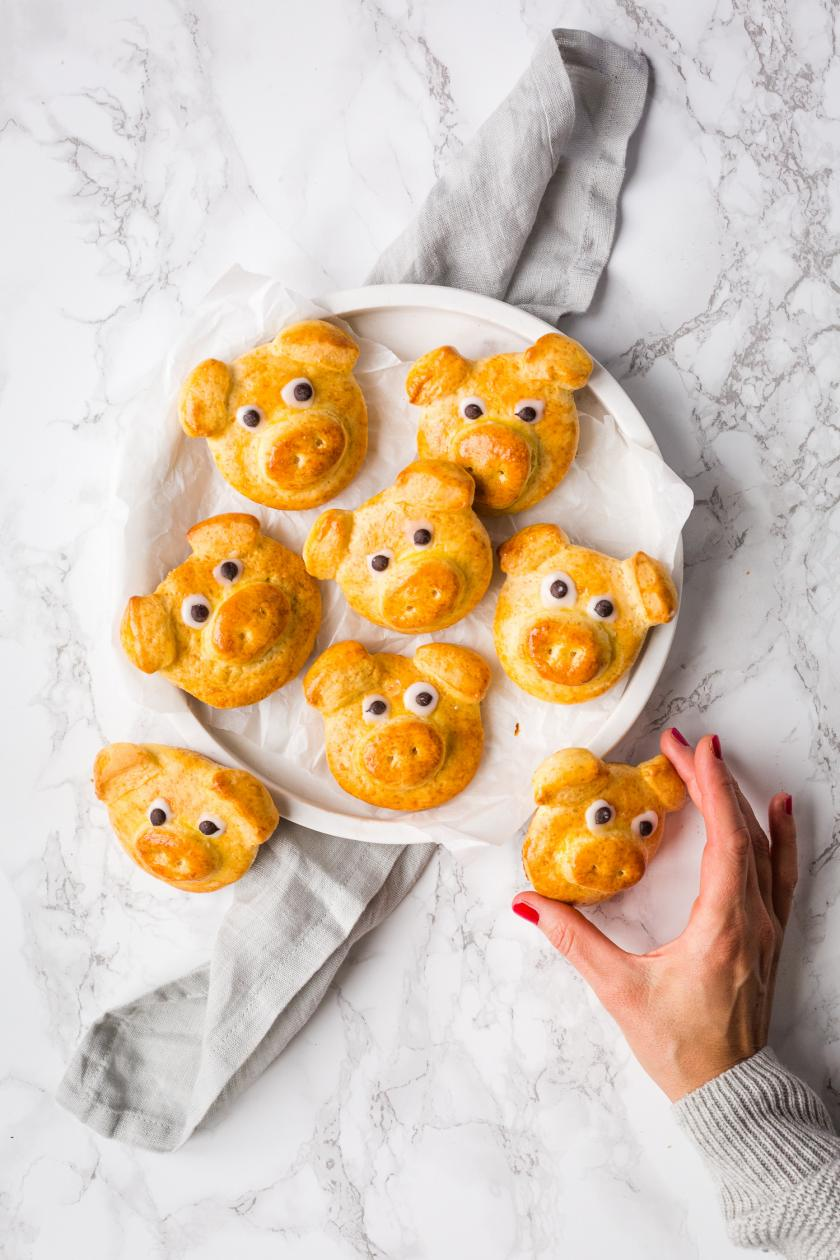 Sieben Glücksschweine aus Quark-Öl-Teig auf einem weißen Teller.