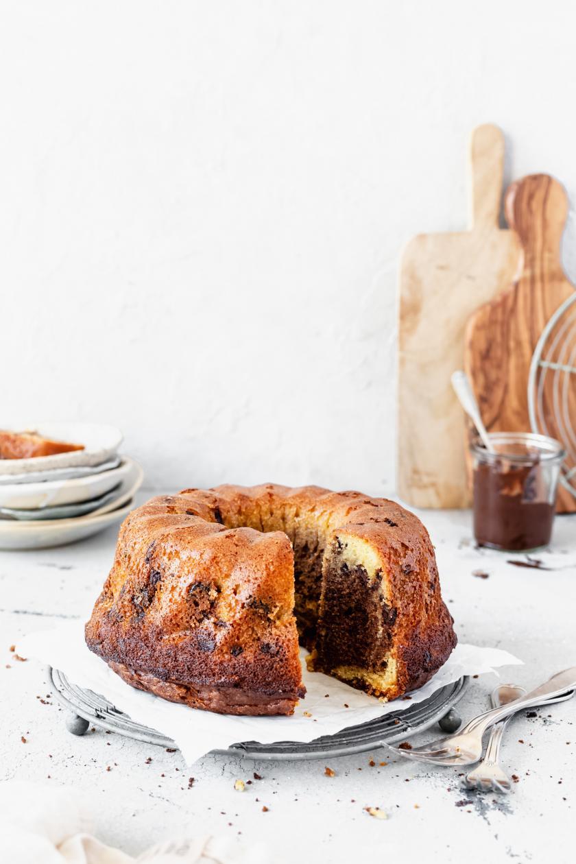 Glutenfreier Marmorkuchen angeschnitten auf einer Kuchenplatte.