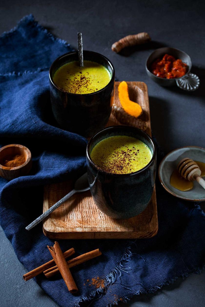 Goldene Milch in zwei Bechern auf einem gedeckten Tisch.