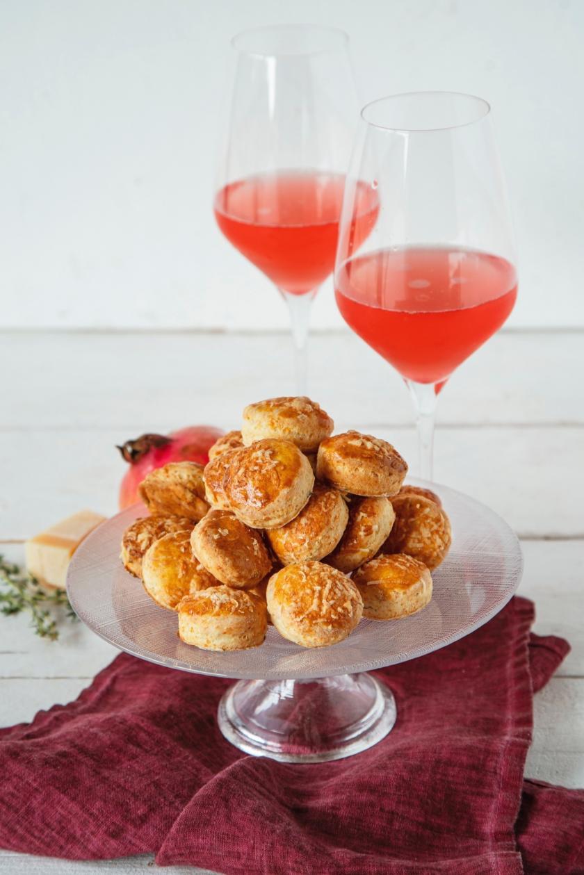 Scones auf Tortenplatte mit zwei Gläsern Granatapfel-Sprizz
