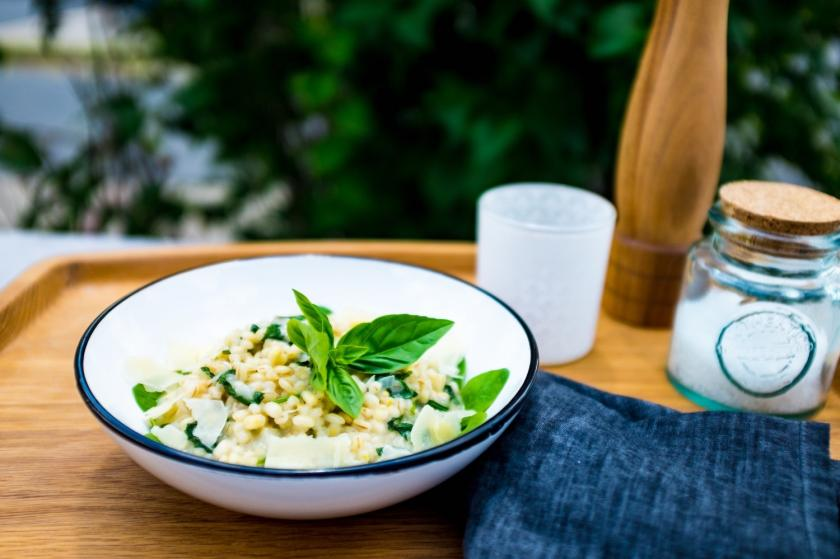 Graupenrisotto mit Spinat in einer Emaille-Schüssel auf Gartentisch