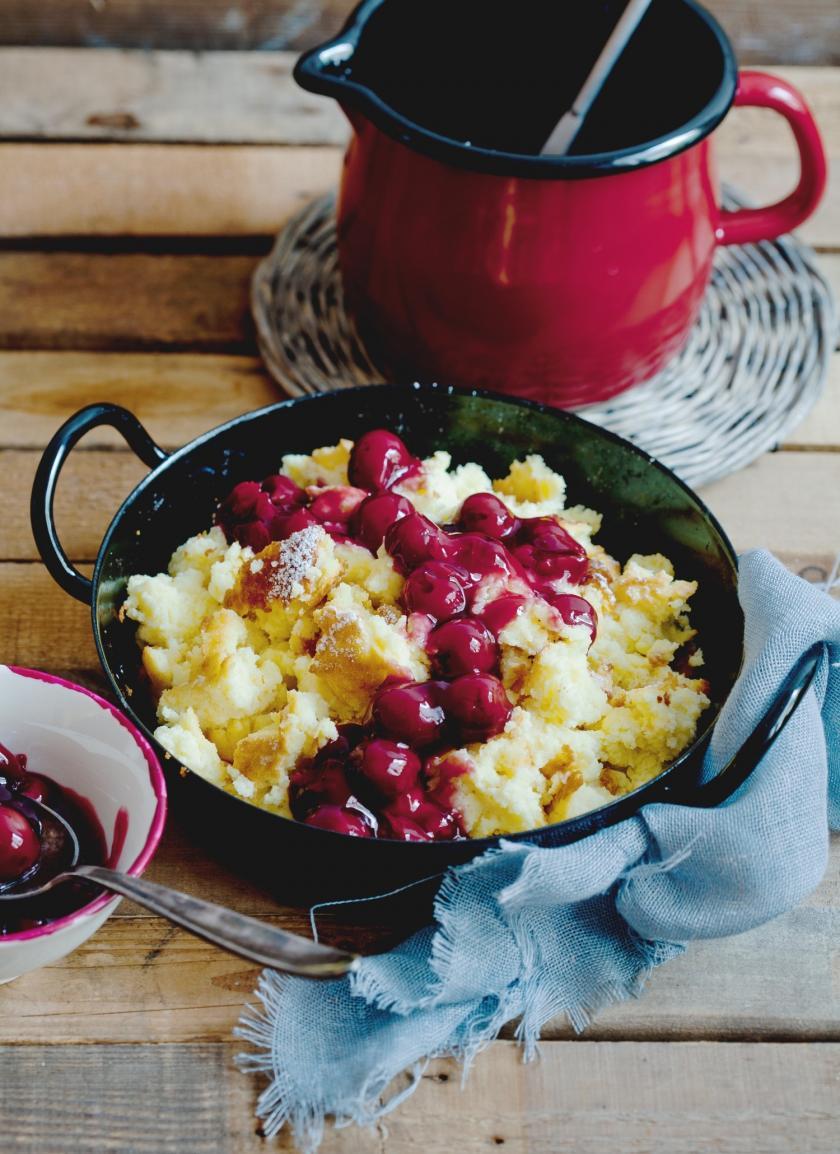 Grießschmarren mit Kirschsoße in einer Pfanne serviert auf einem gedeckten Tisch.