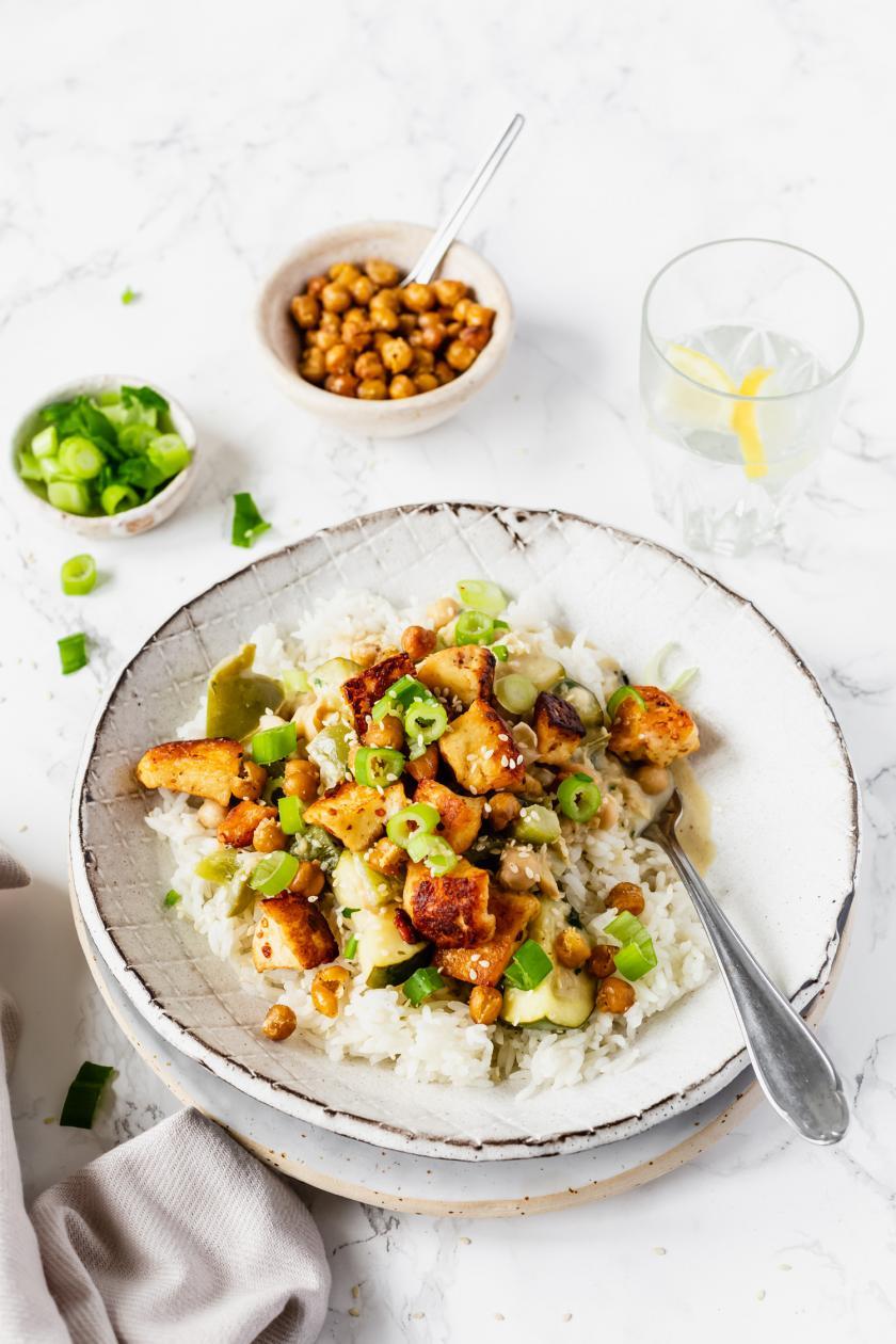 Ein Teller mit grünem Curry mit Halloumi und Kichererbsen.