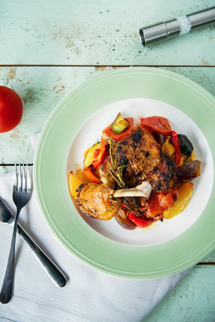 Hähnchenschenkel aus dem Ofen auf Gemüse auf einem Teller.