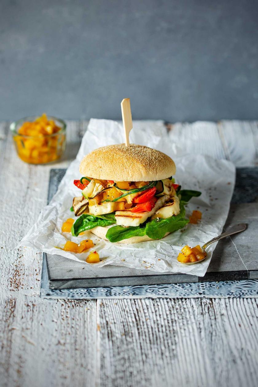 Halloumi-Burger auf Backpapier und Chips im Hintergrund.