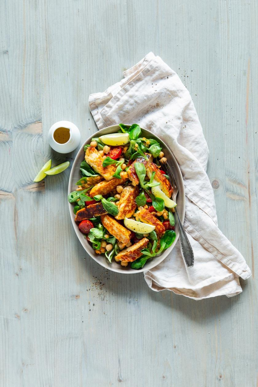 Halloumi-Salat in weißer Schüssel mit Küchentuch.