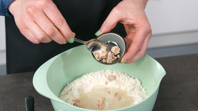 Für die Hefeblume mit rotem Pesto wird Hefe zur Mehlmischung in eine Schüssel gegeben.