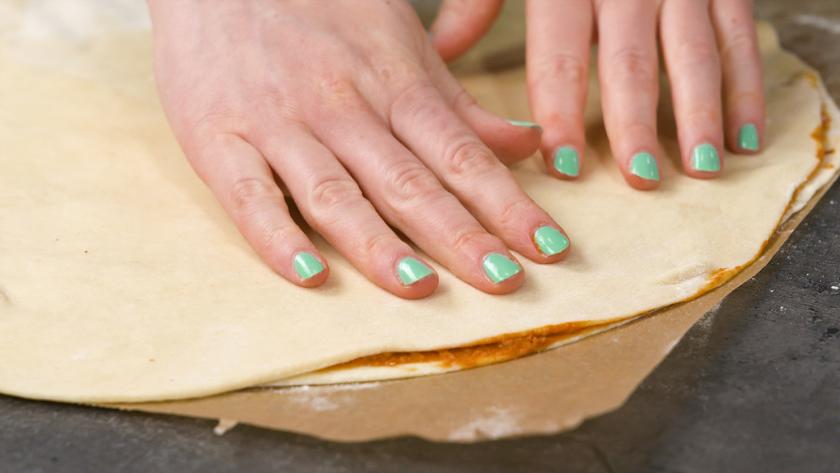 Ein zweiter Teigfladen wird auf den bestrichenen Teig für die Hefeblume mit rotem Pesto gelegt.