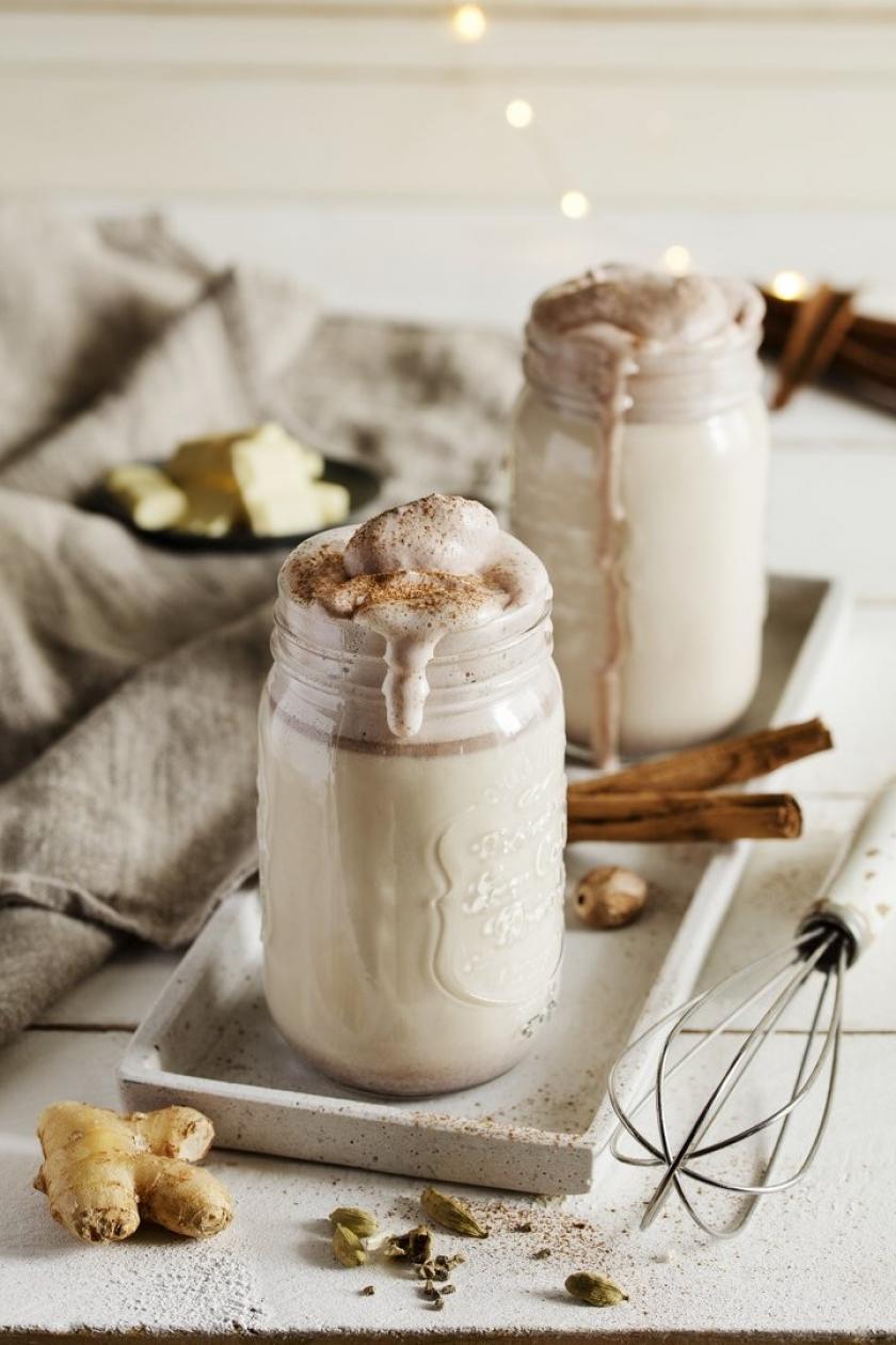 Heiße weiße Schokolade mit Kakaosahne in einem hohen Glas.