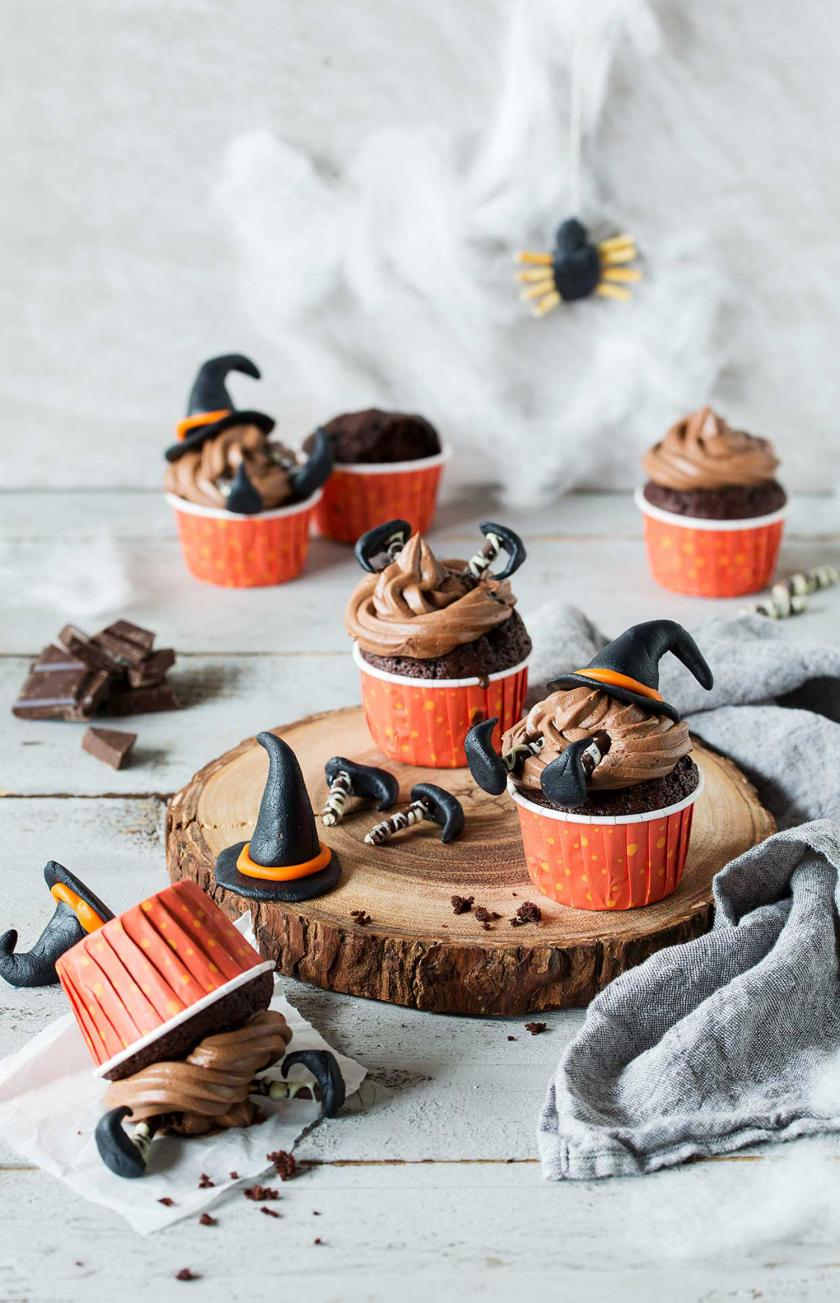 Mehrere Hexen-Cupcakes für Halloween auf einem Tisch angerichtet.