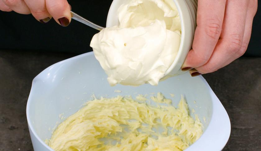 Für das Frosting der Hexen-Cupcakes für Halloween wird Frischkäse zur Butter in eine Schüssel gegeben.