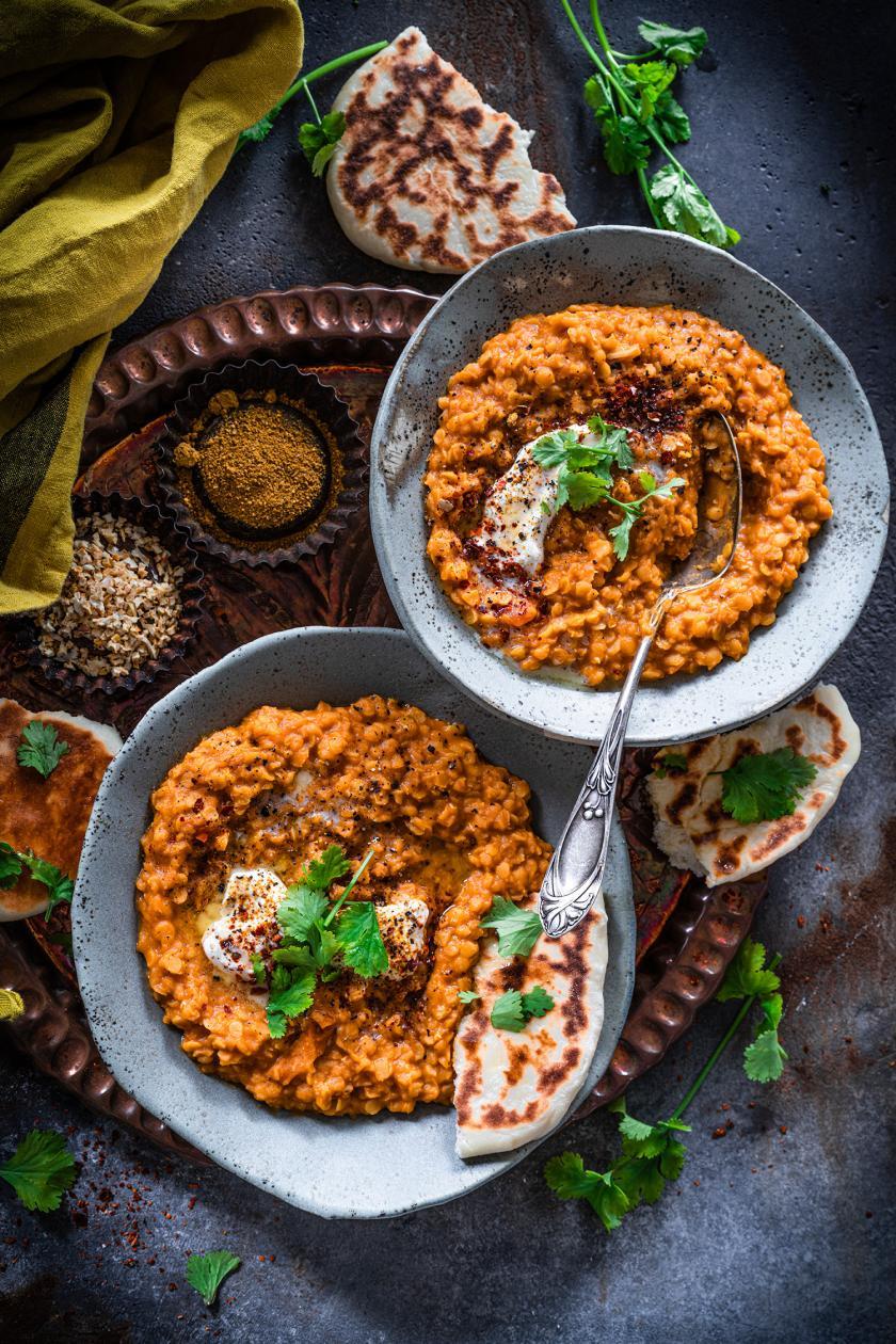 Indisches Dal auf zwei Tellern angerichtet mit Naan-Brot und Gewürzen.