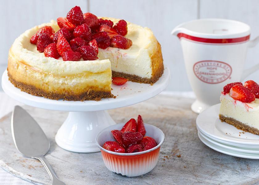 Ein Cheesecake mit Crème fraîche und Erdbeertopping steht angeschnitten auf einer Etagere.