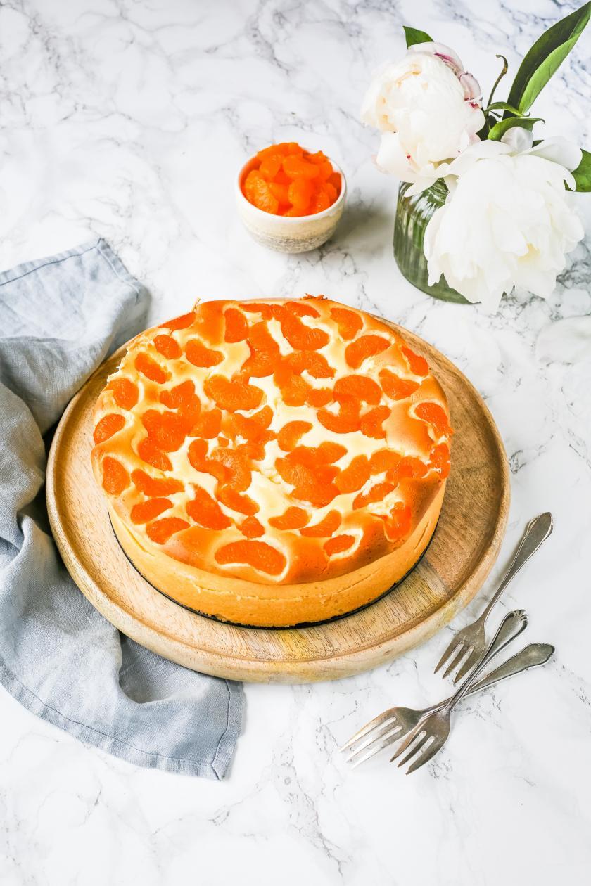 Käsekuchen mit Mandarinen auf Holzbrett