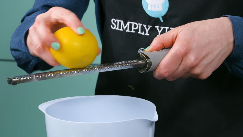 Jemand reibt Zitronenschale über einer Schüssel ab für die Füllung der Käsekuchenmuffins mit Streuseln.