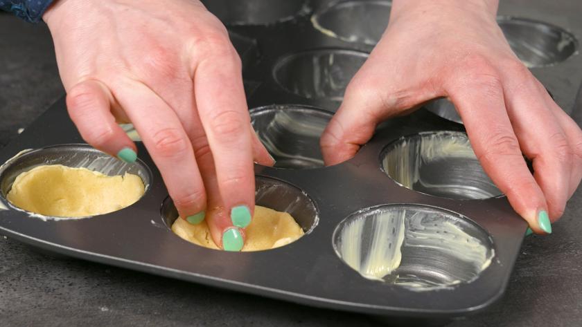 Der Mürbeteig für den Boden der Käsekuchenmuffins mit Streuseln wird in die Muffinförmchen gedrückt.