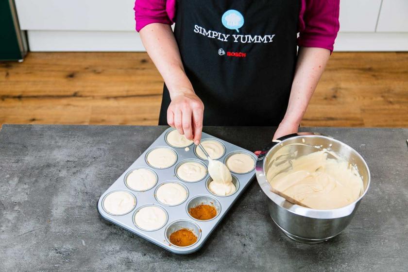 Die Masse für den Karamell-Cheesecake wird auf die Muffinmulden verteilt.
