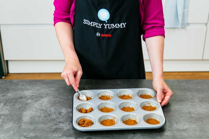 Die Keksmasse wird in eine Muffinform gedrückt.