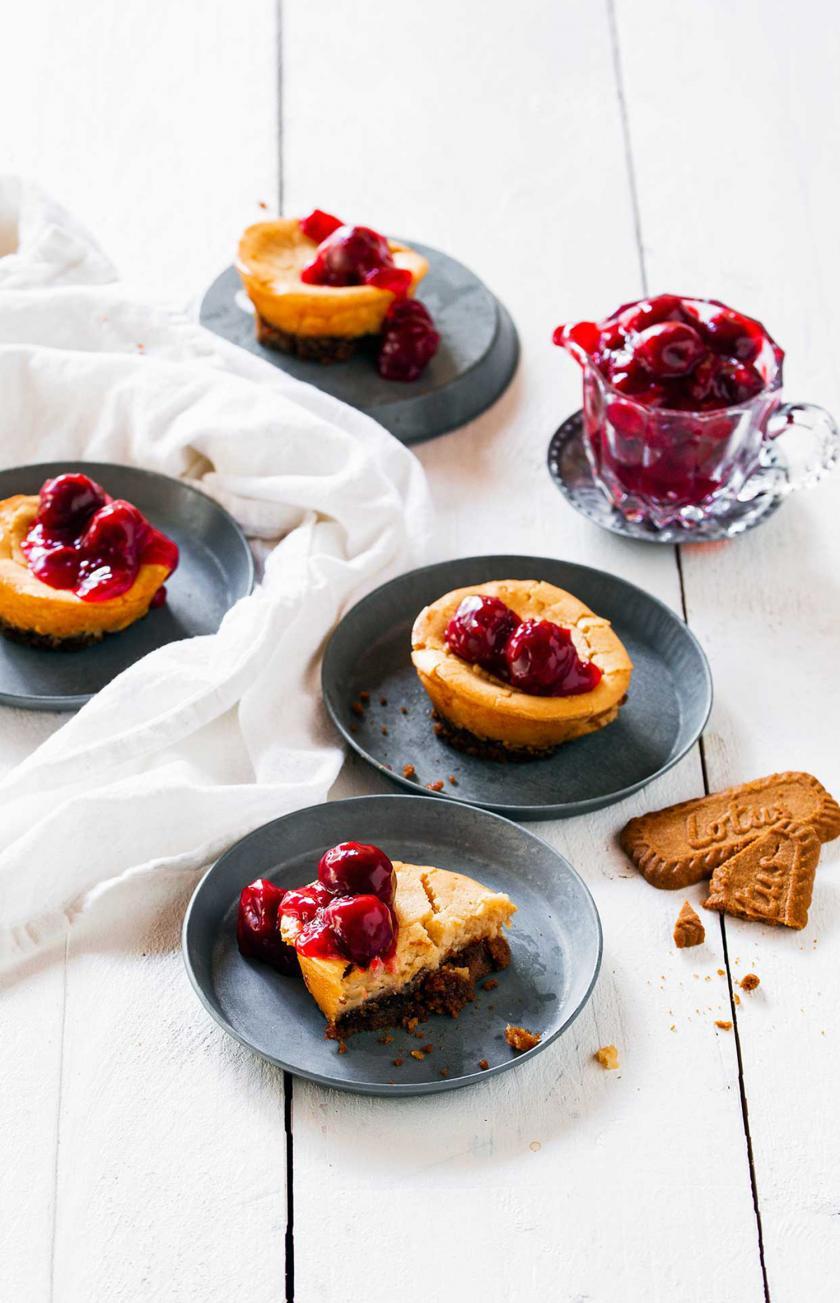 Mehrere Karamell-Cheesecakes mit Kirschen auf Tellern.