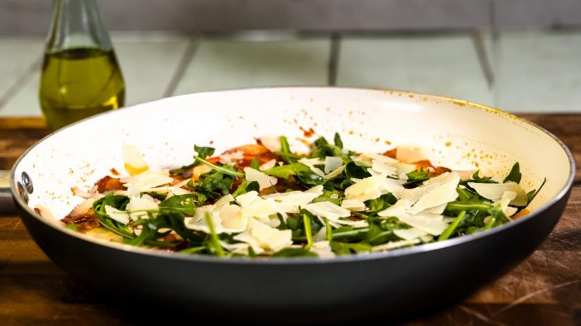 Kartoffelpizza mit Tomaten, Mozzarella und Rucola in der Pfanne gebacken
