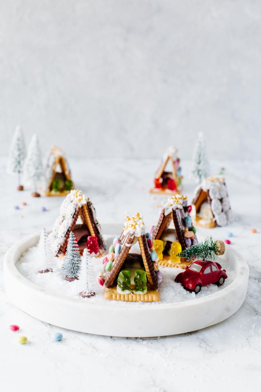 Mehrere Kekshäuser auf weißem Teller.