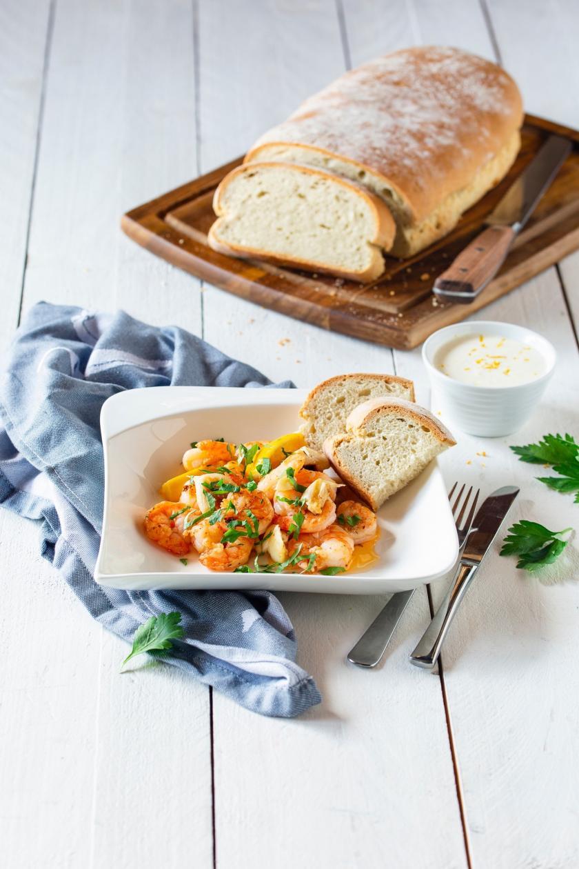 Knoblauchgarnelen auf Teller mit zwei Scheiben Brot.