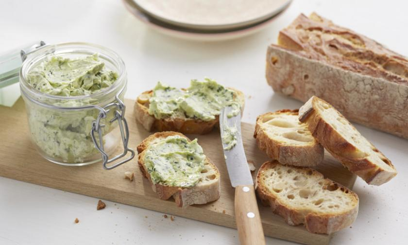 Kräuterbutter auf Brot und einem Brettchen.