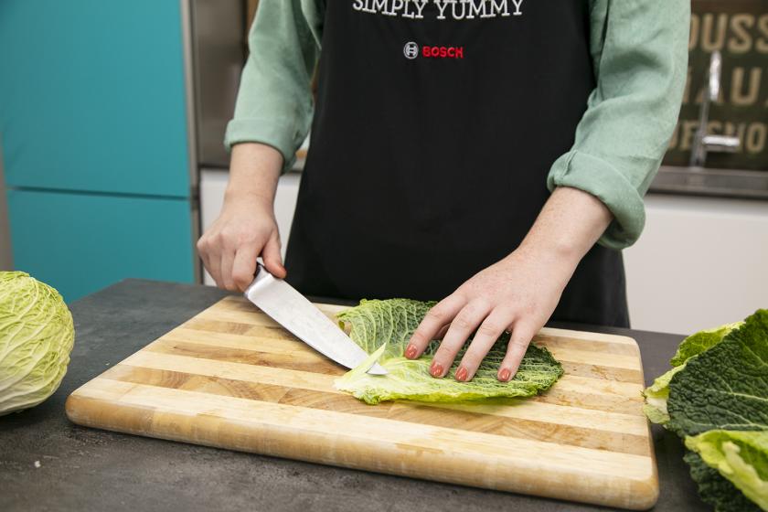 Für die Krautwickel wird der Strunk eines Wirsingblatts weg geschnitten.