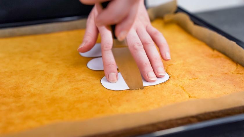 Der Teig für die Kuchen am Stiel wird mit Hilfe einer Schablone ausgeschnitten.
