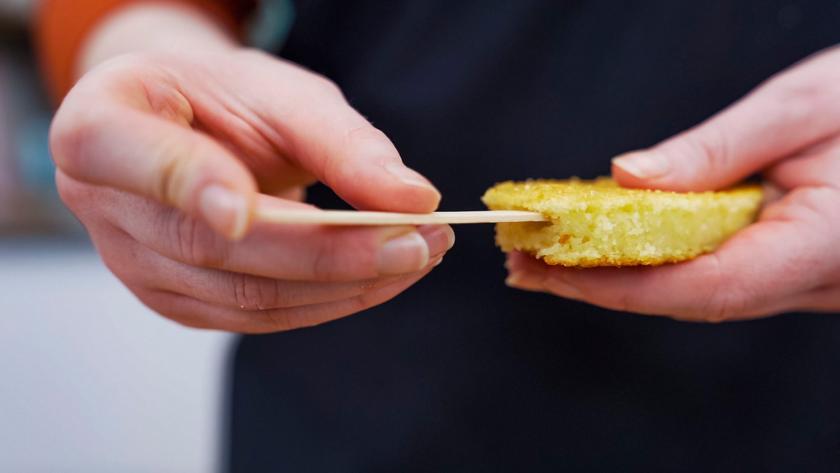 Die ausgeschnittenen Kuchen werden mit einem Holzstäbchen versehen.