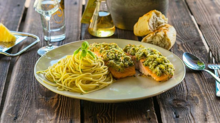 Lachs mit Kräuterkruste und Zitronenspaghetti auf dem Teller.