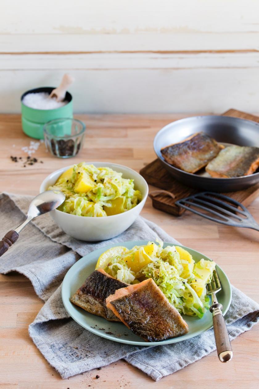 Lachsforelle auf Kartoffel-Spitzkohl-Gemüse auf zwei Tellern angerichtet.