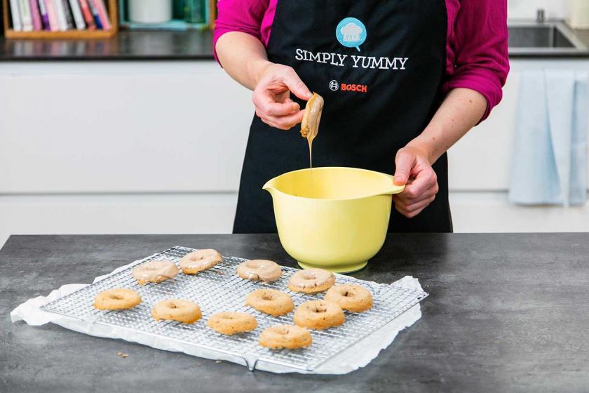 Lebkuchen-Donuts werden in die Glasur getunkt.