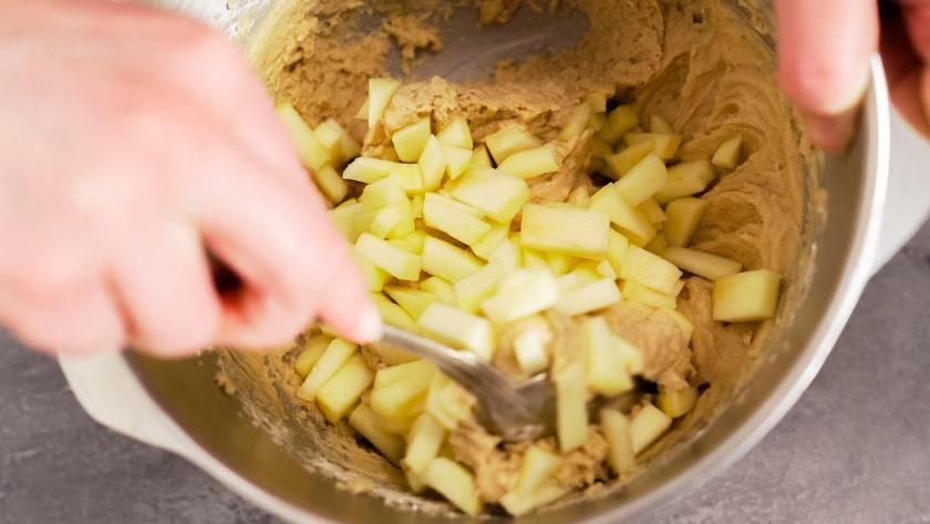Apfelstücke werden unter den Teig der Low Carb Apfelmuffins gehoben.