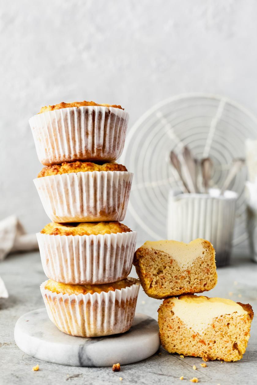 Low Carb Carrot-Cake-Muffins mit Cheesecake-Kern übereinander gestapelt.