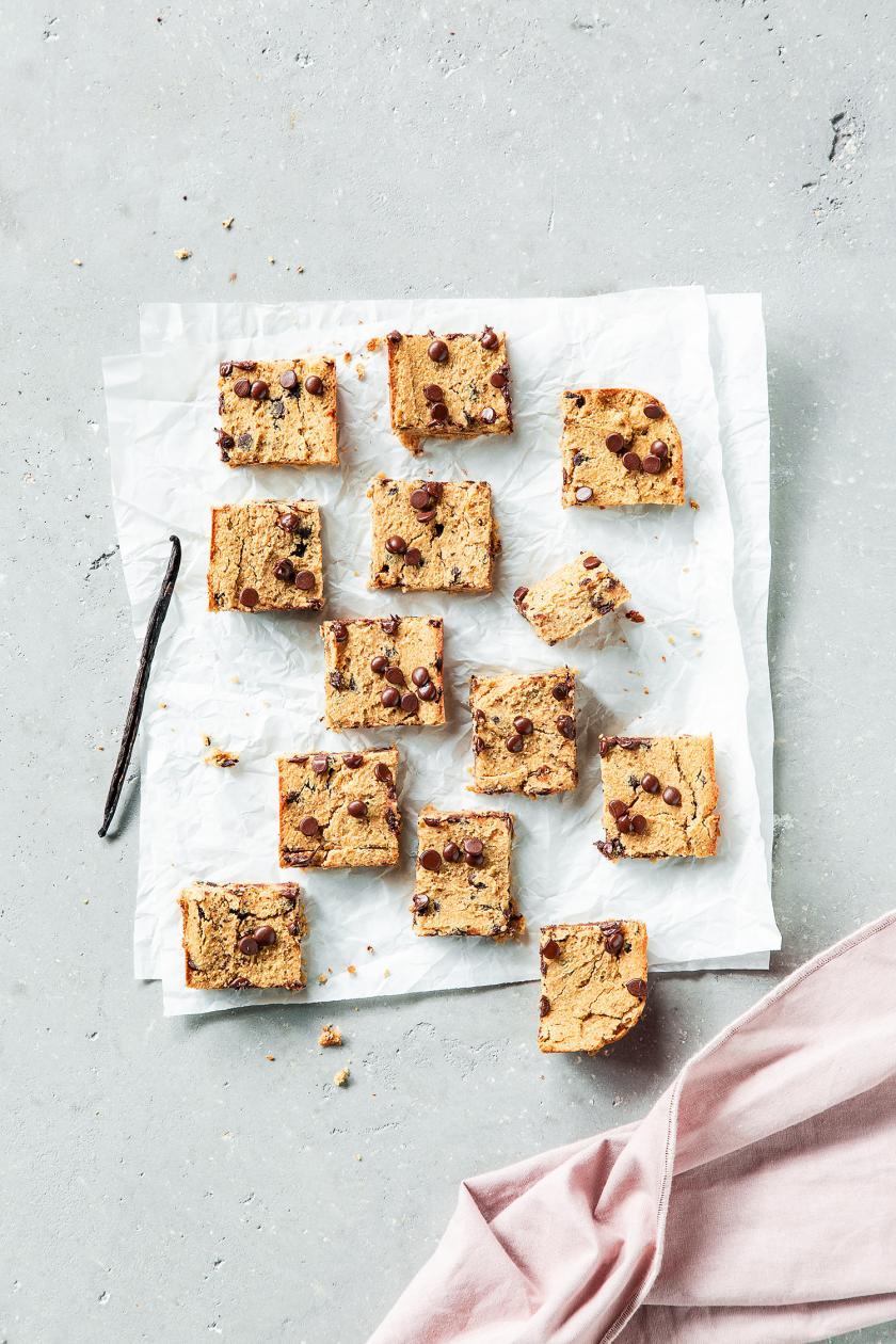 Mehrere Low Carb Cookies in Quadrate geschnitten auf einem Stück Backpapier.