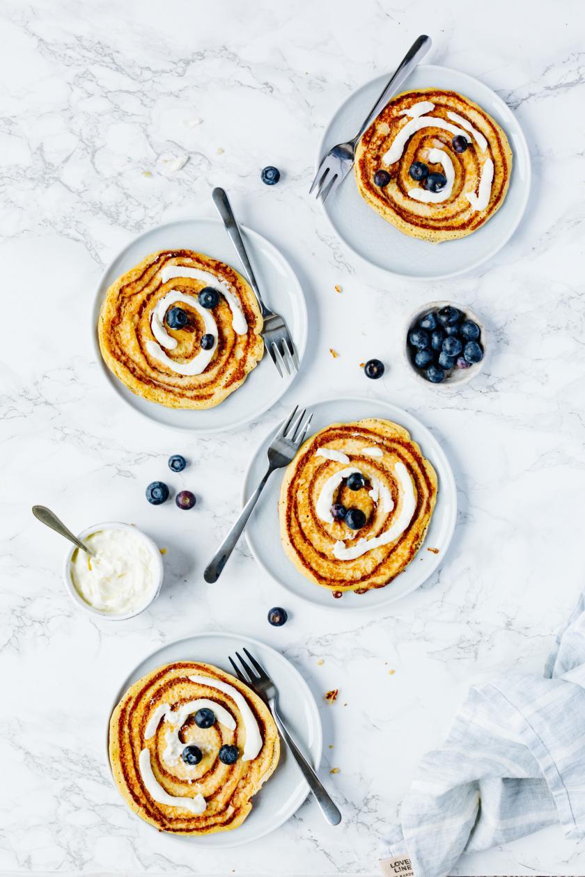 Vier Low Carb Zimtschnecken-Pfannkuchen auf Tellern mit Beeren.