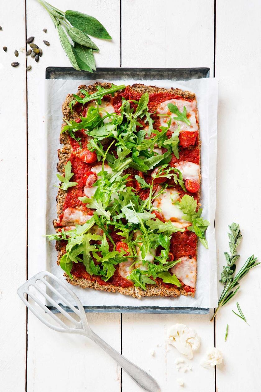 Blumenkohlpizza mit Tomaten,Mozzarella und Rucola liegt auf einem Stück Backpapier auf einem Backblech.