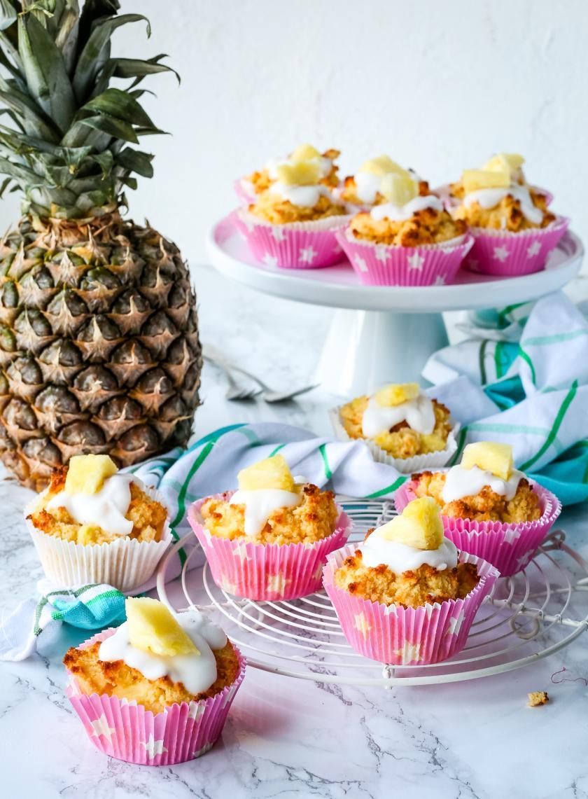 Mehrere Low Carb Kokos-Ananas-Muffins sind vor und auf einer Etagere angerichtet. Im Hintergrund steht eine Ananas.