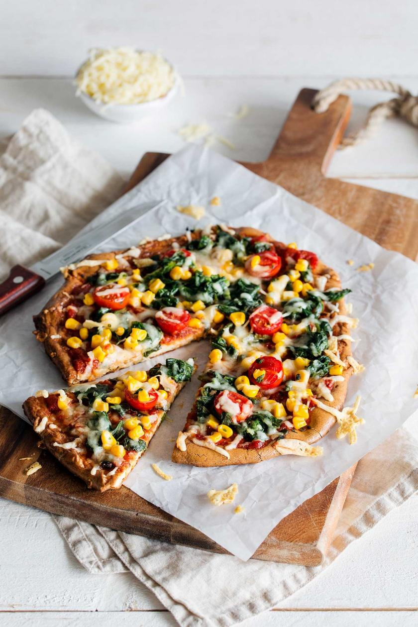 Low Carb Pizza mit Käseboden, Spinat, Mais und Tomaten liegt in Stücke geschnitten auf einem Brett.