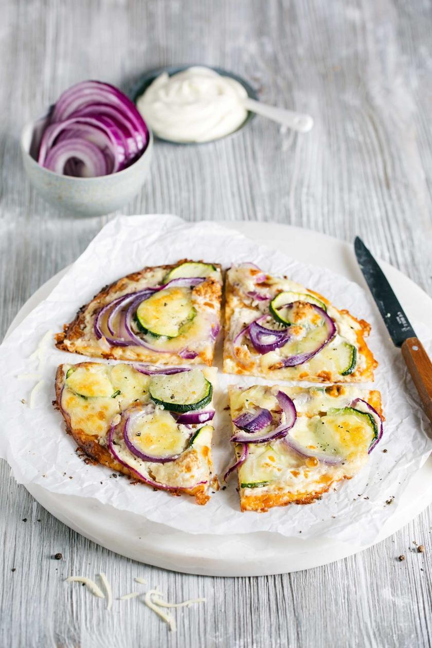 Die Low Carb Pizza mit Quark ist geviertelt und auf einem Teller angerichtet.