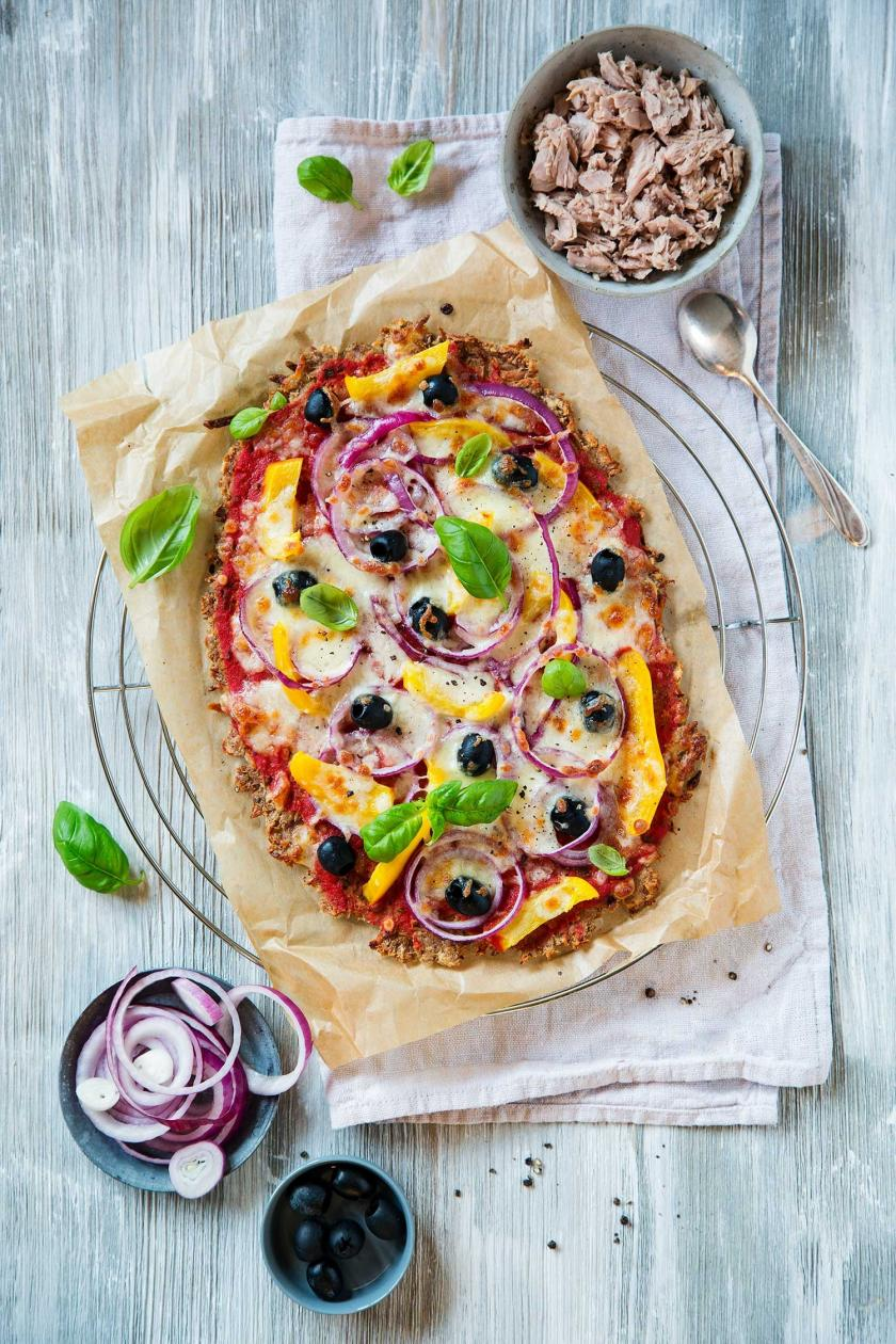 Eine Low Carb Pizza Thunfisch liegt auf einem Stück Backpapier auf einem Holztisch.