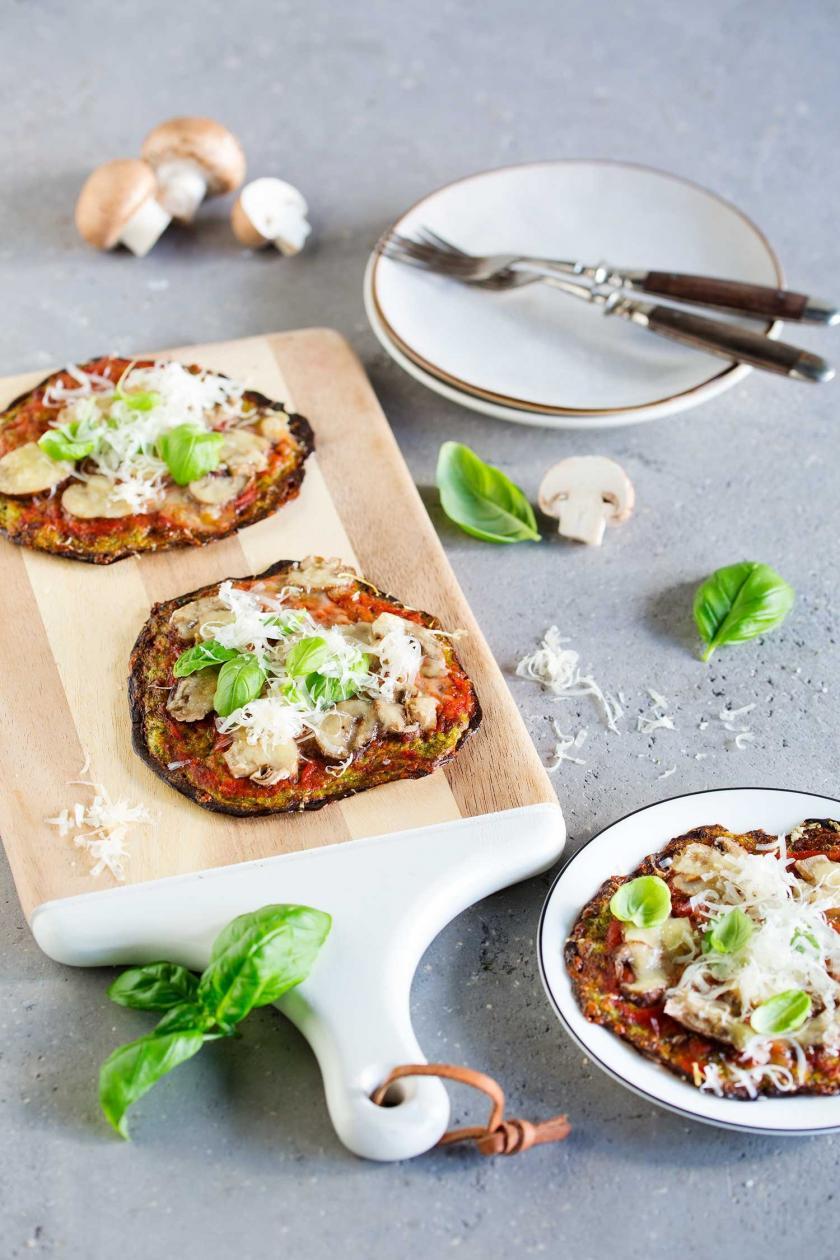 Drei kleine Low Carb Pizzas mit Zucchiniboden auf einem Holzbrett und einem Teller angerichtet.