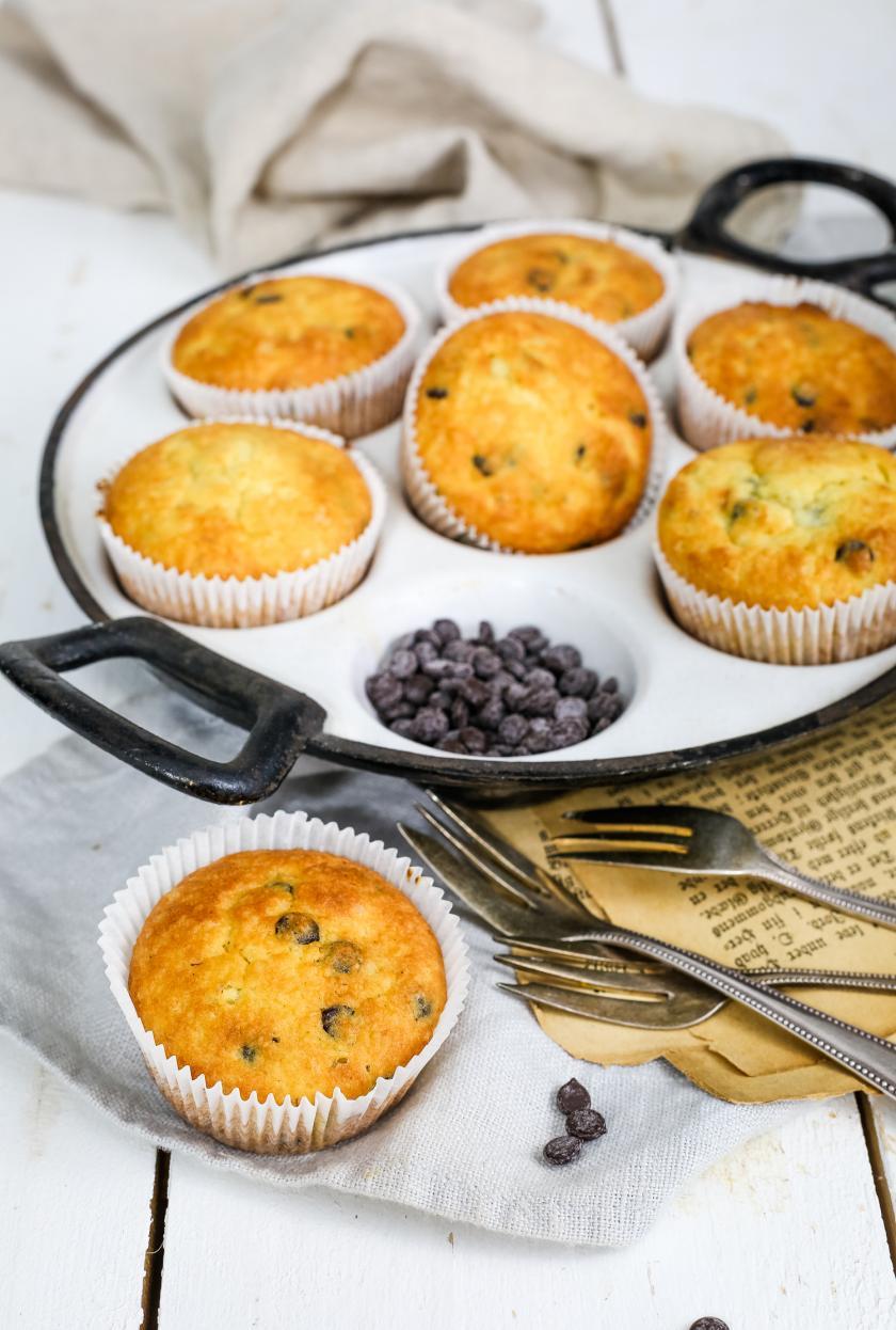 Sieben Low Carb Schokomuffins mit Vanille liegen in einer Muffinsform auf einem Tisch.